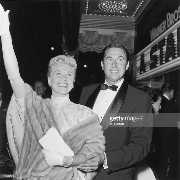 American actor and singer Doris Day waves while standing next to her husband and agent, Marty Melcher, at the premiere of director George Cukor's...