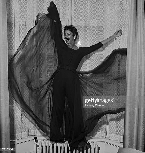 American actor and singer Dorothy Dandridge strikes a pose standing on a radiator in a bay window 26th April 1956