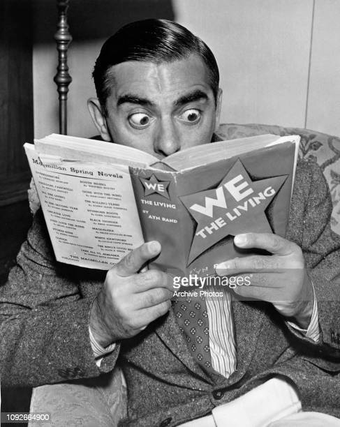 American actor and singer Eddie Cantor reading 'We The Living' by Ayn Rand' circa 1945