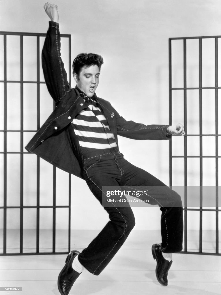 American actor and singer Elvis Presley (1935 - 1977) dancing in a stylized prison uniform in a promotional portrait for director Richard Thorpe's film, 'Jailhouse Rock.'