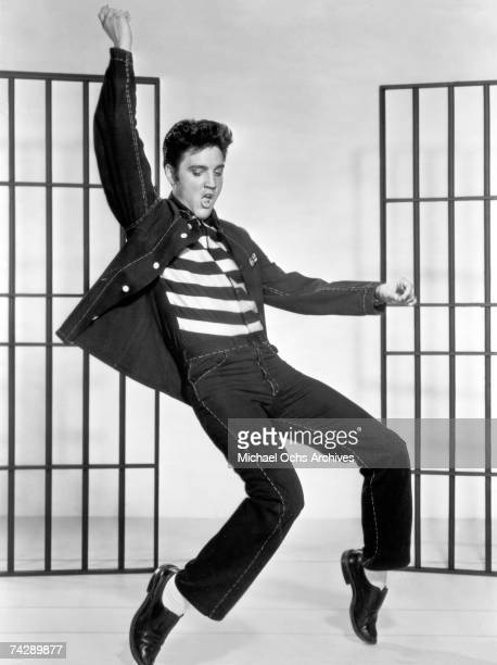 American actor and singer Elvis Presley dancing in a stylized prison uniform in a promotional portrait for director Richard Thorpe's film 'Jailhouse...