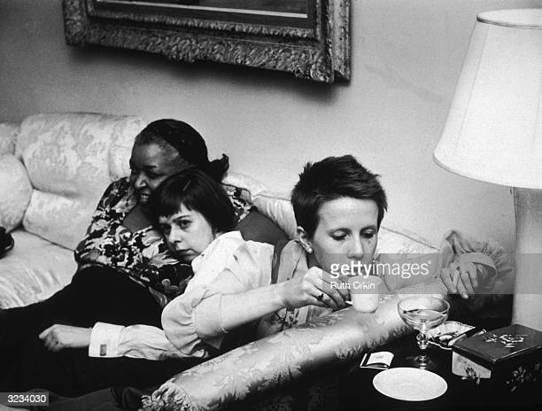 American actor and singer Ethel Waters hugs American author Carson McCullers as actor Julie Harris sips coffee and smoke a cigarette on the set of...