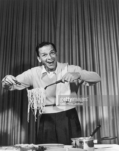 American actor and singer Frank Sinatra clowning around with spaghetti for an EKCO products commercial on the set of CBSTV's 'The Frank Sinatra Show'