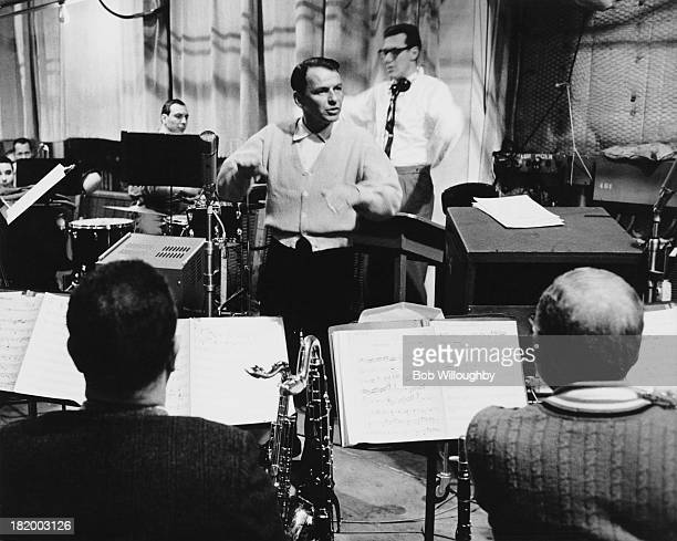 American actor and singer Frank Sinatra conducting musicians in a studio, 1962. The band are working from the score of 'I See Your Face Before Me'.