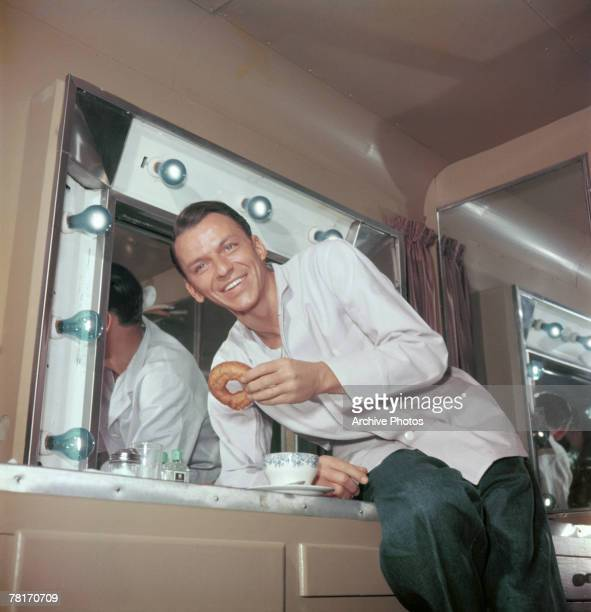 American actor and singer Frank Sinatra enjoys coffee and donuts in his trailer during a break in filming circa 1950