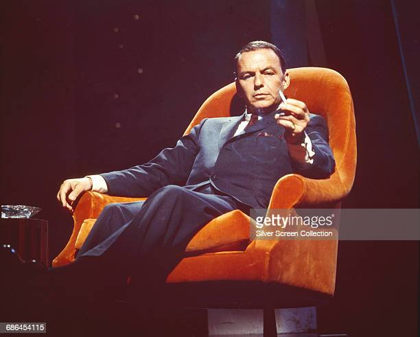 American actor and singer Frank Sinatra in an orange armchair circa 1955