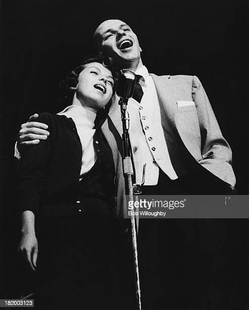 American actor and singer Frank Sinatra performs a duet on stage with his daughter Nancy at University High School in Los Angeles, October 1955....