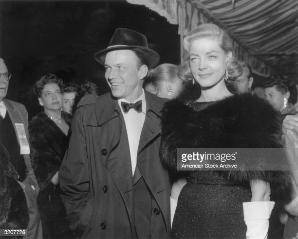American actor and singer Frank Sinatra with American actor Lauren Bacall smiling at a formal event Sinatra is wearing a dark raincoat over a tuxedo...