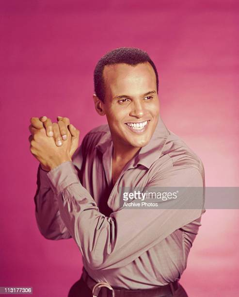 American actor and singer Harry Belafonte poses with his hands clasped circa 1956.
