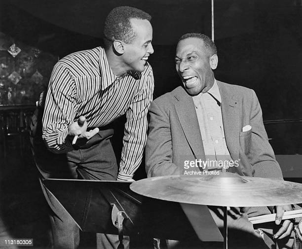 American actor and singer Harry Belafonte sharing a joke with drummer Cozy Cole circa 1957