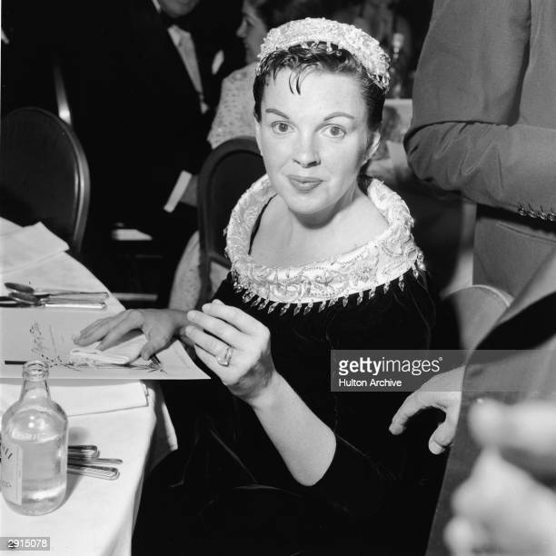 American actor and singer Judy Garland sits at a table at the premiere of the film 'A Star Is Born' directed by George Cukor 1954