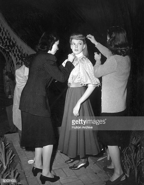 American actor and singer Judy Garland stands while a woman from wardrobe and a makeup artist work on her on the set of director Vincente Minnelli's...