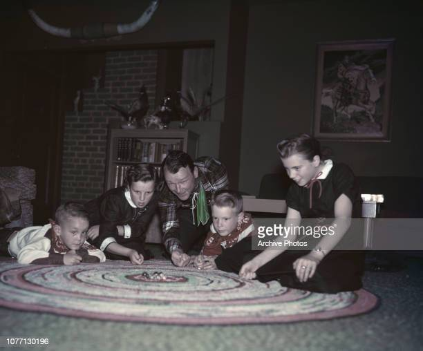 American actor and singer Roy Rogers playing marbles with his children in the family living room, circa 1955. From left to right, Sandy, Marion...
