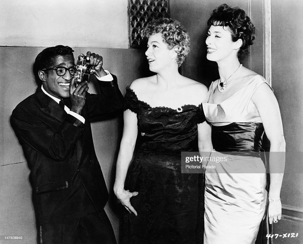 American actor and singer Sammy Davis, Jr (1925 - 1990) photographs actresses Shelley Winters (1920 - 2006, centre) and Rita Gam at the Waldorf-Astoria Hotel, New York City, 18th December 1956. They are attending a supper dance after the premiere of Elia Kazan's 'Baby Doll'.