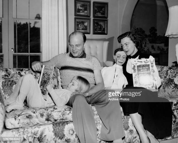 American actor and ventriloquist Edgar Bergen reads 'The Golden Christmas Book' to his daughter Candice while his wife actress Frances née Westerman...