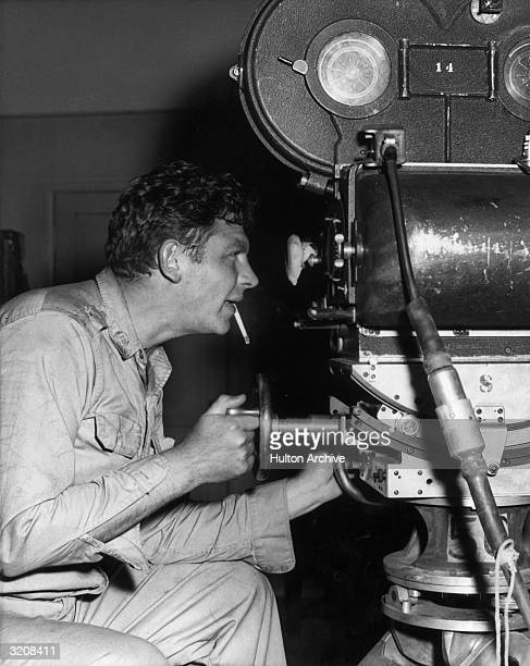 American actor Andy Griffith sits behind the motion picture camera looking through the eyepiece and smoking a cigarette on the set of director Mervyn...