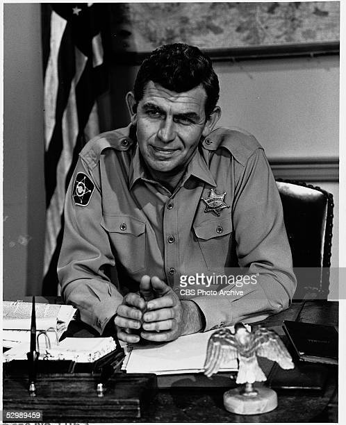 American actor Andy Griffith sits in uniform behind a desk on the set of his television series 'The Andy Griffith Show,' 1967.