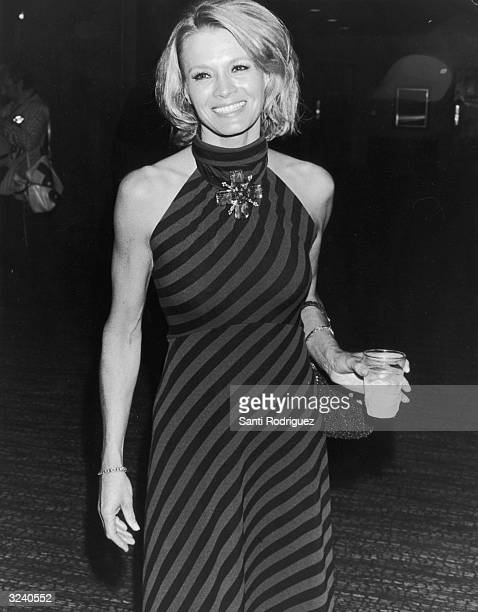 American actor Angie Dickinson of the television series 'Police Woman' smiles and holds a drink as she attends an event She wears a striped dress