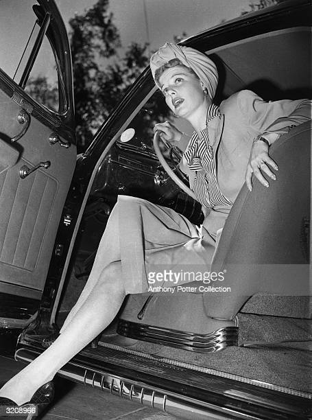 American actor Ann Sheridan prepares to exit an automobile while promoting cotton stockings during World War II Nylon stockings had been rationed as...