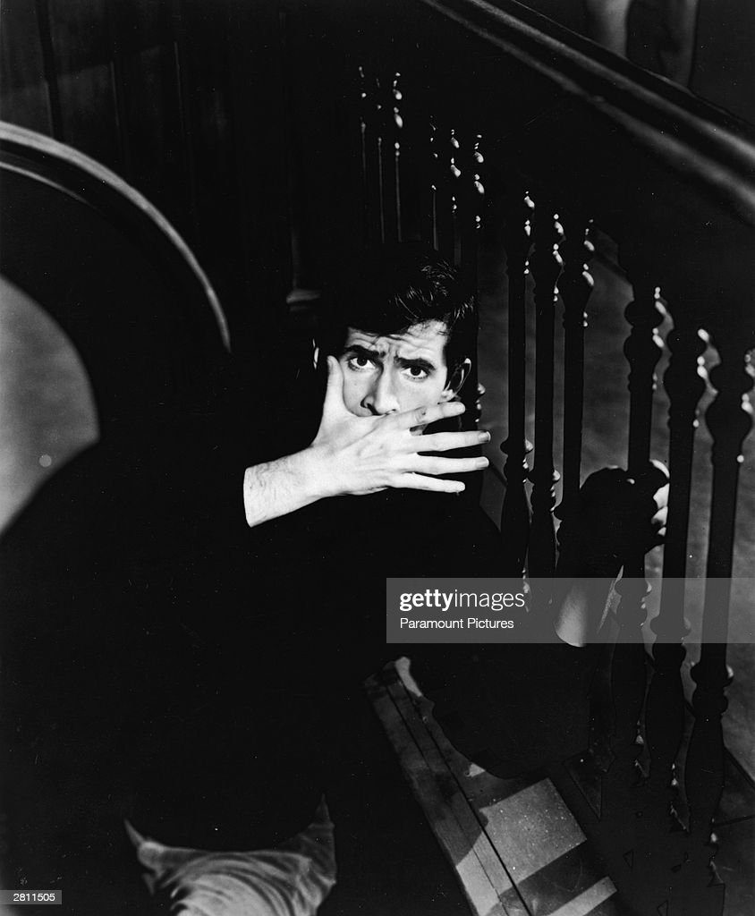 American actor Anthony Perkins (1932 - 1992) covers his mouth and holds onto a banister in a scene from 'Psycho,' directed by Alfred Hitchcock, 1960.