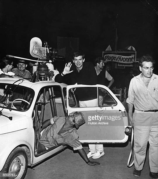 American actor Anthony Perkins leans against a car and waves on the set of director Andre Cayatte's film 'Le Glaive et le Balance' JuanLesPins France...