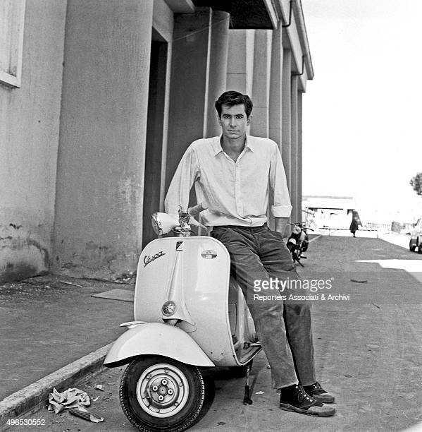 American actor Anthony Perkins posing on a Vespa in the streets of Cinecittà Rome 1957