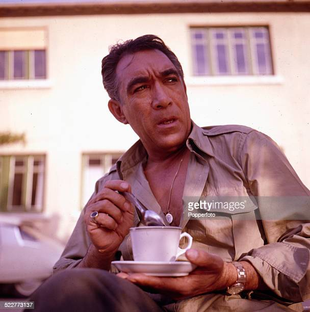 American actor Anthony Quinn posed holding a cup of tea on location in 1963