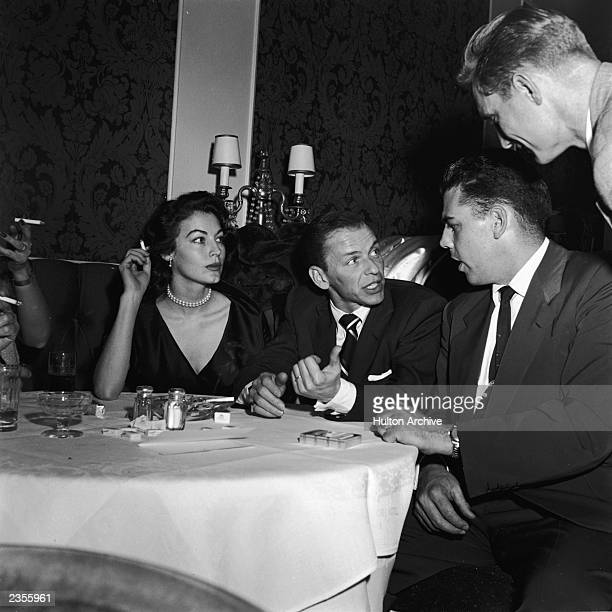 American actor Ava Gardner and her husband American singer and actor Frank Sinatra chat with Cleveland Browns football player Otto Graham during a...