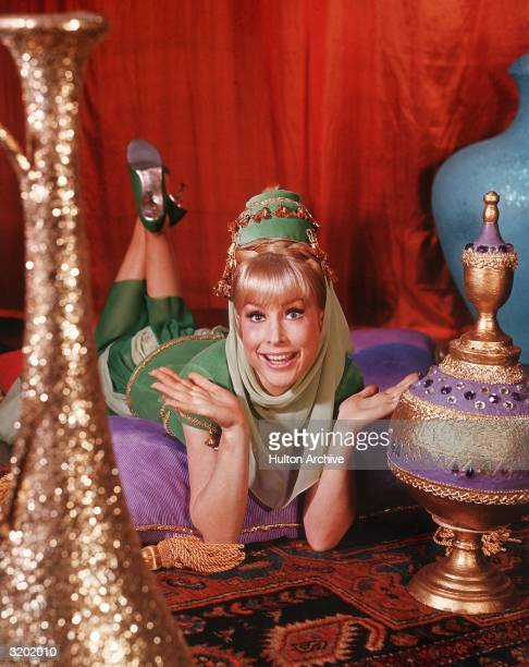 American actor Barbara Eden holds her hands up and smiles while lying on her stomach on top of cushions on an oriental rug in a promotional portrait...