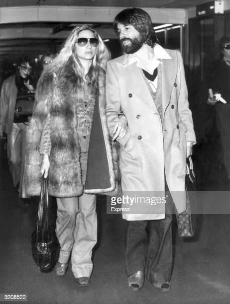 American actor Barbra Streisand walks with her boyfriend Jon Peters in London Airport before the Royal premiere of director Herbert Ross's film...