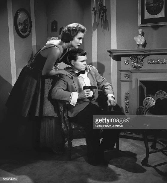 American actor Barry Nelson sits in a chair and aims a gun at an unseen assailant as actress Linda Christian rests on his shoulders in an episode of...