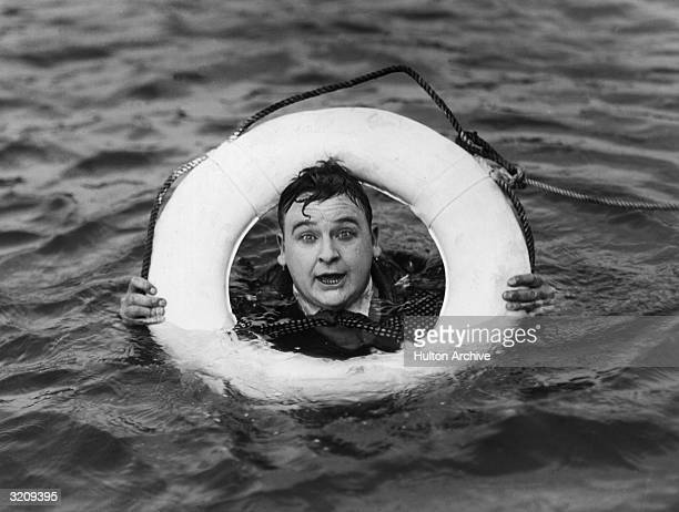American actor Bert Roach clings to a life preserver in a still from director Archie Mayo's film 'Money Talks'