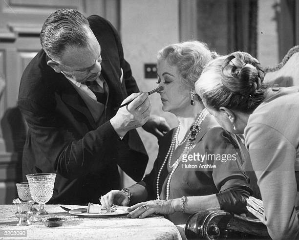 American actor Bette Davis has her nose touched up by a makeup artist with a brush on the set of director Edward Dmytryk's film, 'Where Love Has...