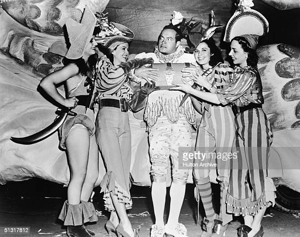 American actor Bob Hope tries to protect his box of treasure from a band of lovely ladies in a still from the film 'Louisiana Purchase,' featuring...