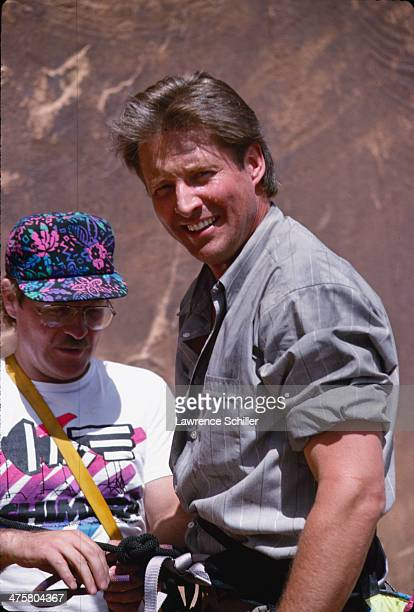 American actor Bruce Boxleitner is hooked into a harness by an unidentified crewmember in preparation for a rock climbing scene in the tv movie...