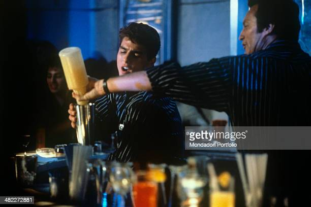 American actor Bryan Brown pouring something in the cocktail mixer of American actor Tom Cruise in the film Cocktail 1988
