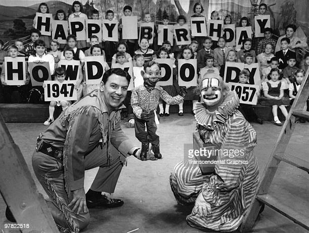 American actor Buffalo Bob Smith poses with marionette Howdy Doody and Lew Anderson along with an audience of children on the set of the Howdy Doody...