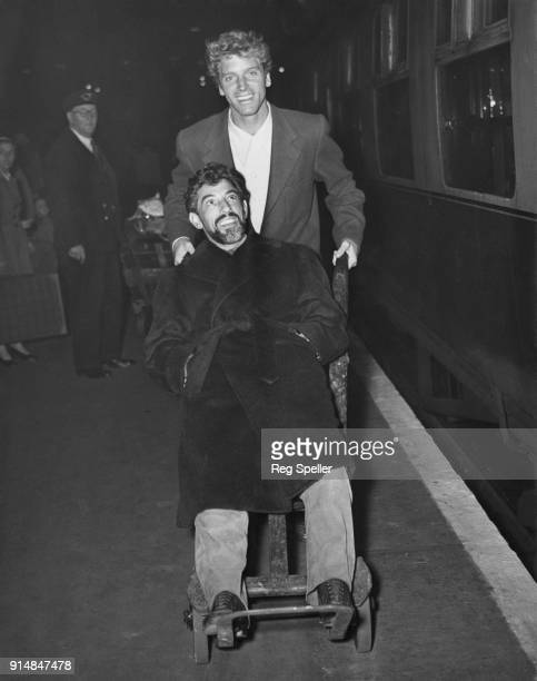 American actor Burt Lancaster arrives at Victoria Station in London with actor and stuntman Nick Cravat whom he is wheeling on a luggage trolley 17th...