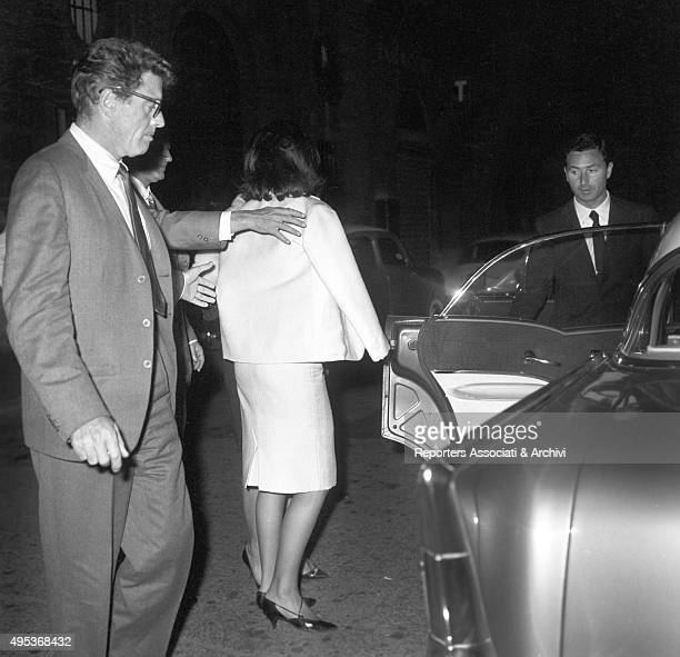 American actor Burt Lancaster going to get into a car with French actress and model Beatrice Altariba, turned and wearing a white suit. Rome,
