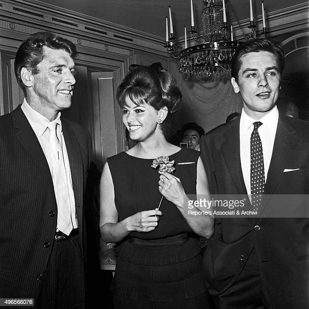 American actor Burt Lancaster Italian actress Claudia Cardinale smiling with a flower in the hands and French actor Alain Delon being photographed by...