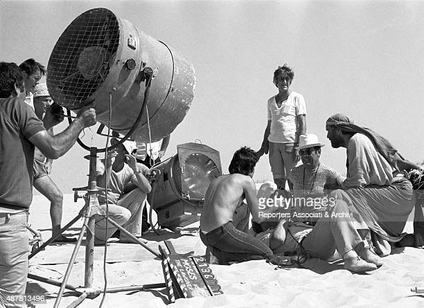 American actor Burt Lancaster pausing on the set of the movie Moses sitting on the sand with some crew members 1974