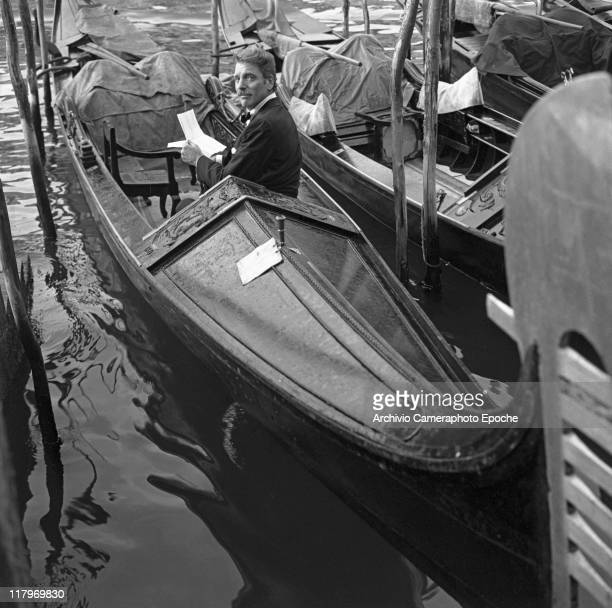 American actor Burt Lancaster portrayed from behind wearing a tuxedo and a bow tie and reading a letter sitting on a gondola stationary among other...