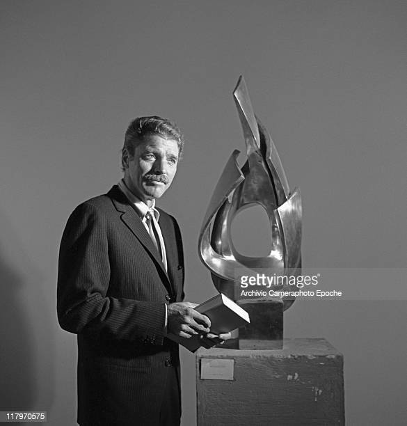 American actor Burt Lancaster wearing a pinstriped suit and a tie holding a book portrayed next to a sculpture during the Art Biennale exhibition...