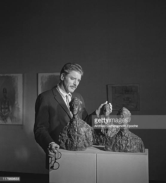 American actor Burt Lancaster wearing a pinstriped suit and a tie holding glasses portrayed while caressing Alberto Giacometti's 'Bustes' at the Art...