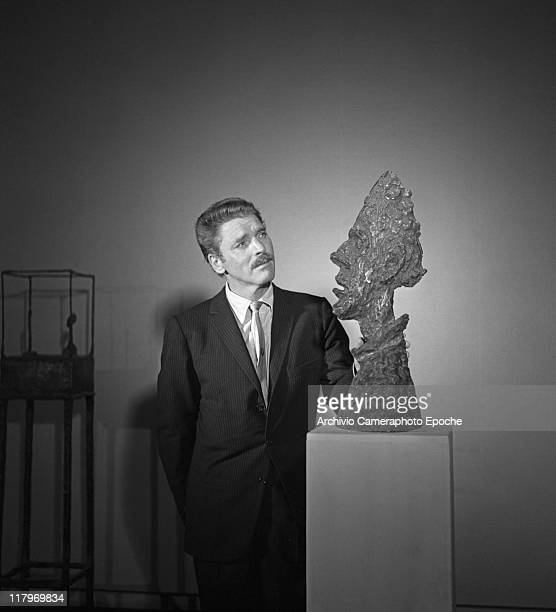 American actor Burt Lancaster wearing a pinstriped suit and a tie portrayed while standing next to Alberto Giacometti's sculpture 'La Grande Tete de...