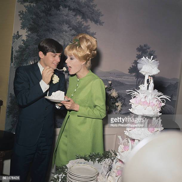 American actor Burt Ward who plays the role of Robin in the television series Batman pictured with his bride Kathy Kersh eating a slice of wedding...