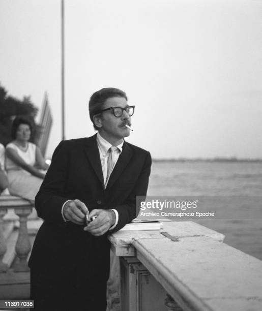American actor Burton Stephen 'Burt' Lancaster looking at the lagoon leaning on a balustrade wearing a suit a black glasses smoking a cigarette...