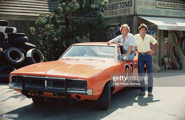 American actor Byron Cherry sits in the window of the 'General Lee,' the famous orange Dodge Charger from the television series 'The Dukes of...