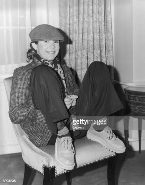 American actor Carrie Fisher sits with her feet up on a chair and her legs spread apart She wears a cap a silk scarf a tweed blazer trousers argyle...