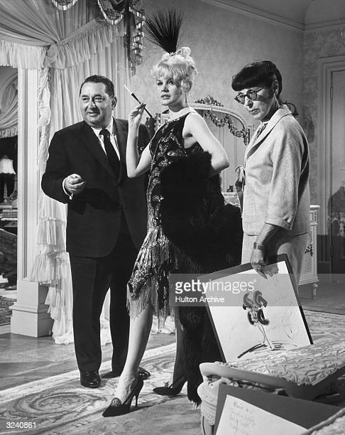 American actor Carroll Baker wears a costume from the film 'Harlow' which was designed by American costume designer Edith Head who is holding a...